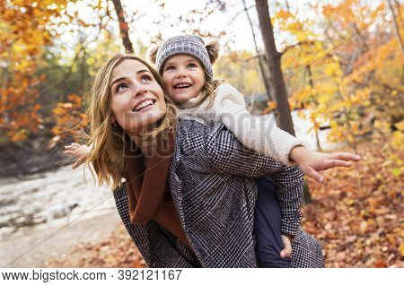 Little Girl And Her Mother Playing In The Autumn Park With Child On Back