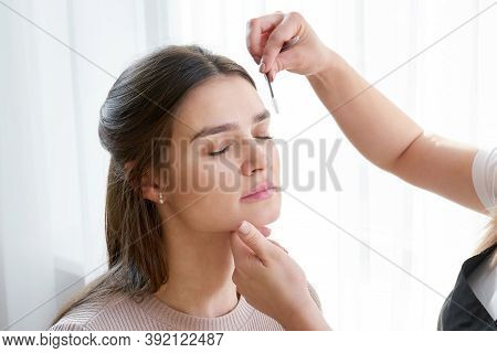 Plucking Female Eyebrows With Tweezers During Eyebrow Correction In Beauty Salon