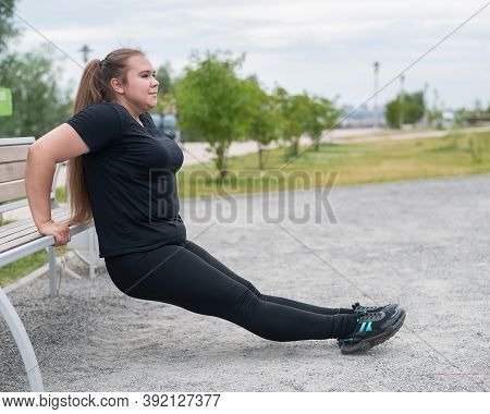 Young Fat Woman Doing Push-ups From The Bench Outdoors. Chubby Girl Doing Fitness Exercises.