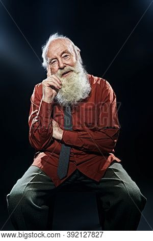 Old age concept. Portrait of an old man with white beard calmly looking at camera. Black background.