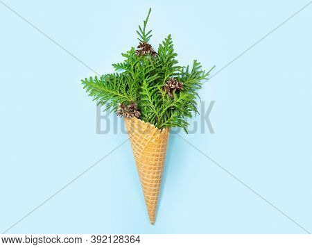 Ice Cream Cone With Thuja Sprigs. Blue Background. New Year Card. Copy Space, Flat Lay. The Concept