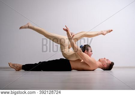 A Duet Of Acrobats Showing A Pair Trick. A Woman In Gymnastics Overalls In A Handstand Over A Shirtl