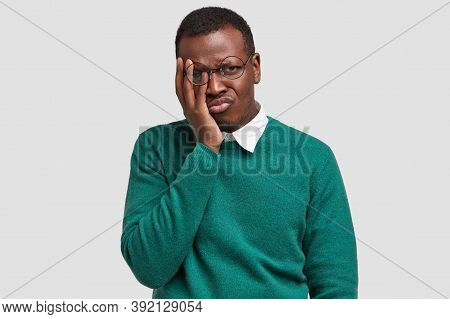 Cheereless Pity Dark Skinned Guy Touches Face With Palm, Looks In Displeasure Through Round Spectacl