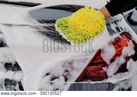 Back View Of Mans Hand With Sponge Washing Car Hood And Lights. Black Auto Covered With Foam. Close