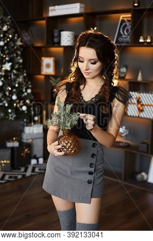 A Young Woman In A Grey Skirt, Stockings And Black Blouse Holds Christmas Decoration In Interior