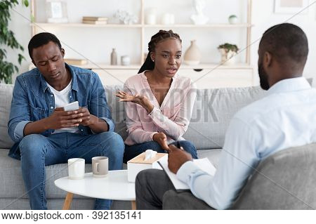 Smartphone Addiction. Annoyed African Wife Complaining About Her Indifferent Husband To Family Couns