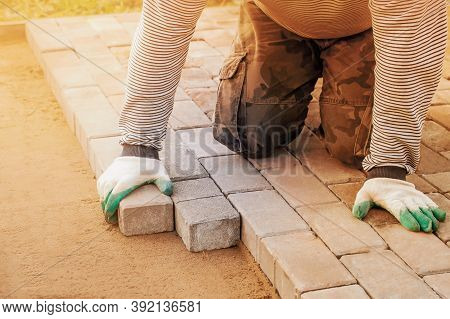 Man In Gloves Lays Paving Stones In Layers On Garden Pathway.  Laying Gray Concrete Paving Slabs In