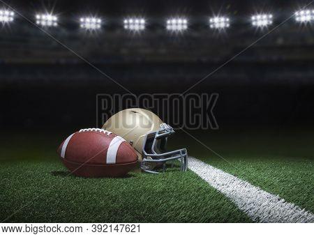 Football And Gold Helmet On Grass Field Below Stadium Lights At Night