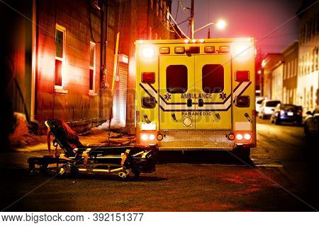 An Ambulance Car Parked On The Side Street At Night