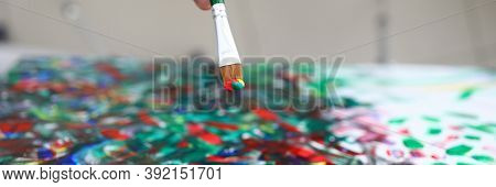 Top View Of Person Creating New Masterpiece With Paintbrush. Mans Hand Holding Brush And Applying Co
