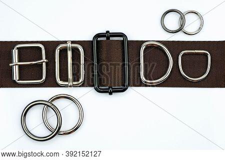 Brown Belt With Adjusters, Buckles, Rings, Half Rings Top View. Metal Bag Accessories On A Belt Stra