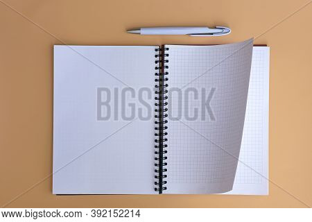 Spring Notepad, Checkered Sheets  Top View. Checkered Notebook With A Flip Sheet On A Beige Backgrou