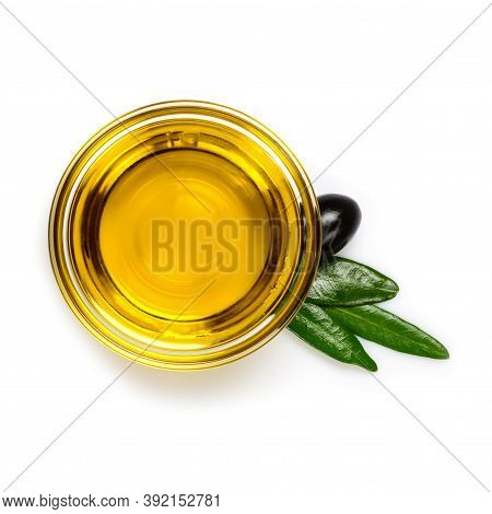 Olive Oil. Extra Virgin Olive Oil In Glass Transparent Bowl With Leaves And One Black Olive. Close-u