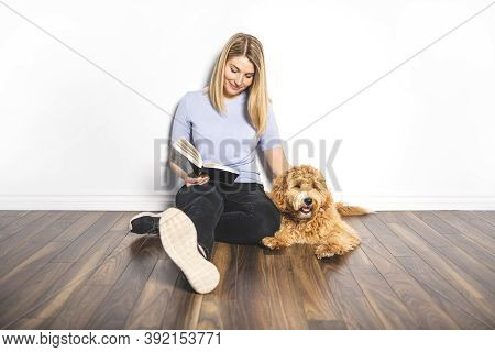 Woman With His Golden Labradoodle Dog Reading Book Isolated On White Background