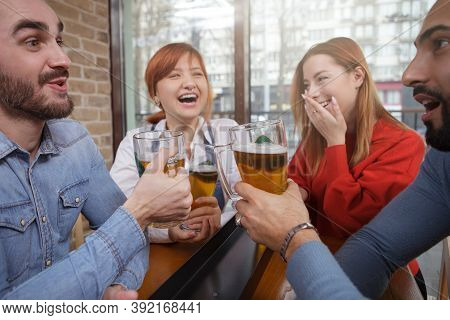 Cheerful Friends Laughing And Talking Over A Glass Of Beer At Local Pub. Friendship, Youth Concept