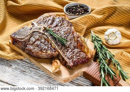 Grilled T Bone Steak On A Chopping Board. Cooked Tbone Beef. White Wooden Background. Top View