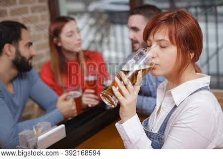 Close Up Of A Young Woman Enjoying Drinking Delicious Beer With Her Friends. Woman Sipping Craft Bee