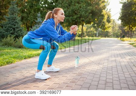 Full Length Shot Of A Beautiful Sportswoman Squatting Outdoors, Copy Space. Attractive Fitness Woman
