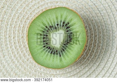 A Kiwe Cut In Half On A Circular Shaped Straw Palcemat.