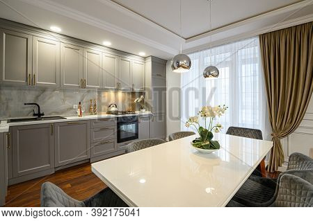 Luxury grey and white contemporary classic kitchen interior with dining table designed in modern style