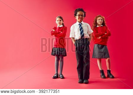 Group Of Elementary School Pupils Wearing Uniform Folding Arms Against Red Studio Background