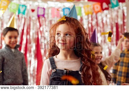 Group Of Children In Party Hats Celebrating At Birthday Party With Streamers And Gold Confetti