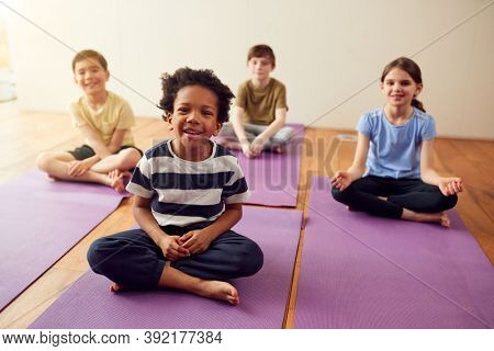 Portrait Of Group Of Children Sitting On Exercise Mats In Exercise Class