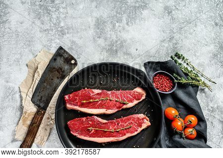 Fresh Raw Sirloin Steak On A Grill Pan. Gray Background. Top View. Copy Space