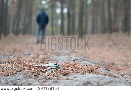 Young Man Loses His Keys Bunch On Russian Autumn Fir Wood Path. Carelessness And Losing Keys Concept