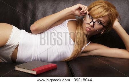 Beautiful young woman lying down on coach with book in sleep wear lingerie.