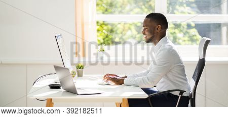 African American Man Sitting At Computer In Office