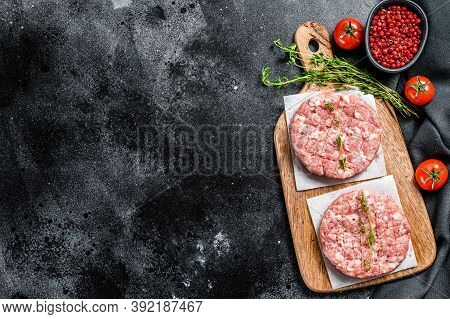 Raw Chicken Patty, Ground Meat Cutlets On A Chopping Board. Organic Mince. Black Background. Top Vie