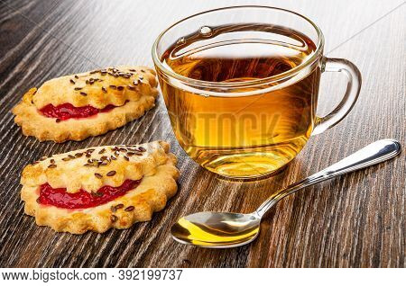 Shortbread Cookies With Raspberry Jam And Linseeds, Transparent Cup With Tea, Teaspoon On Dark Woode
