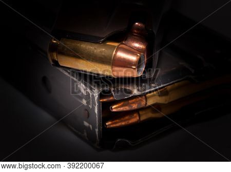 A Handgun Magazine Loaded With .40 Caliber Hollow Point Bullets On Top Of A Rifle Magazine Loaded Wi