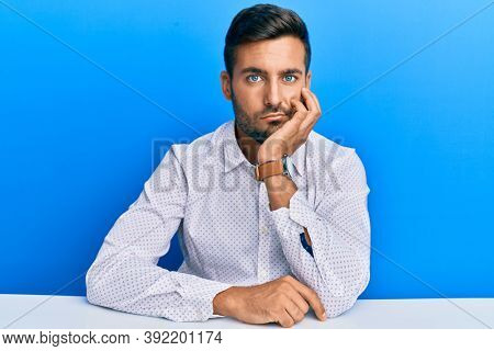 Handsome hispanic man wearing business clothes sitting on the table thinking looking tired and bored with depression problems with crossed arms.