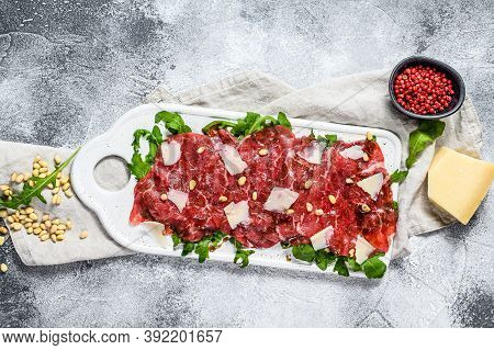 Black Angus Beef Carpaccio With Parmesan Cheese. Gray Background. Top View