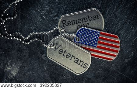 US military soldier's dog tags engraved with Remember our Veteran's text and in the shape of the American flag. Memorial Day or Veterans Day concept.