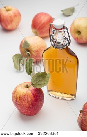 Fresh Ripe Apples And Apple Cider Vinegar. Apple Cider In A Glass Bottle And Fresh Apples. Light Bac
