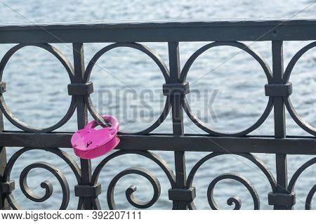 Pink Padlock In Shape Of Heart On Forged Metal Border Of Bridge On The River. Symbol Of Love And Fid
