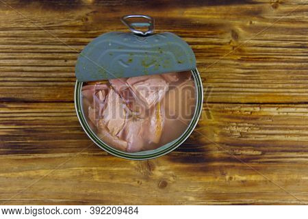 Open Tin Can Of Tuna Fish On A Wooden Table. Top View