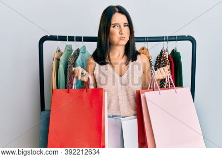 Middle age brunette personal shopper woman holding shopping bags puffing cheeks with funny face. mouth inflated with air, catching air.
