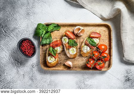 Bruschetta With Tomatoes, Mozzarella Cheese And Basil. Italian Appetizer Or Snack, Antipasto. Gray B