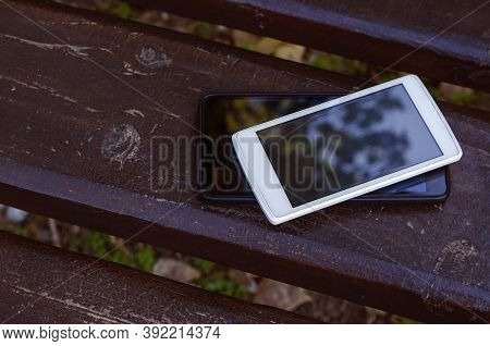 Сoncept Of Love Date Without Phones And Social Networks. Two Smartphones Lie On Park Bench. White An