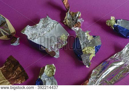 Lots Of Crumpled Shiny Candy Wrappers On Pink Background. Empty Chocolate Candy Wrappers. Leftovers