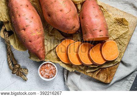 Raw Sweet Potatoes On A Chopping Board, Organic Yam. Farm Vegetables. Gray Background