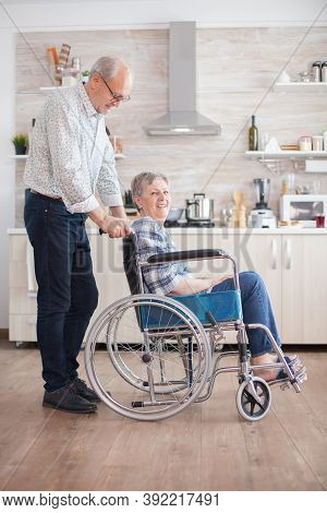 Elderly Retired Man Helping His Wife With Walking Disability. Disabled Senior Woman Sitting In Wheel