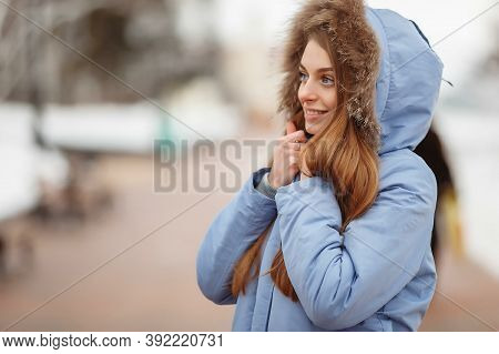 Young Woman Are Walking In The Winter Park. Winter Park In The Snow. Clothing Advertising Photo Conc