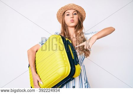 Young caucasian woman with blond hair wearing summer dress and holding cabin bag puffing cheeks with funny face. mouth inflated with air, catching air.