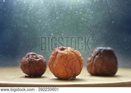 Dry Apples Lie On A Wooden Surface.