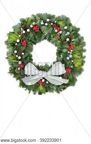 Traditional Christmas spruce fir wreath with winter berry holly, & greenery with bow on white background. Festive composition for the holiday season. Copy space.